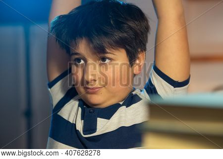 Boy Doing Gymnastic Stretching Between Classes In The Room. Childs Face Against The Background Of Bo