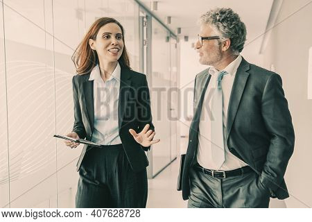 Successful Businesspeople Walking Through Office Corridor And Talking. Professional Senior Executive