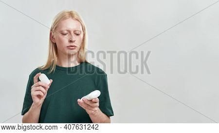 Handsome Young Caucasian Man With Long Fair Hair Choosing Deodorant While Holding Two Samples Standi