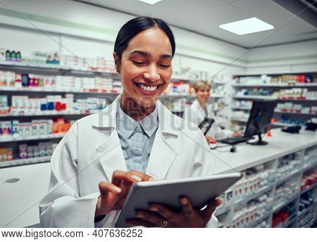 Portrait Of Cheerful Young Woman Browsing Digital Tablet Working In Pharmacy With Colleague In Backg