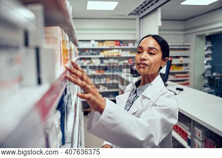 Young Woman Working In Pharmacy Looking For Medicine In Shelf Standing Behind Counter