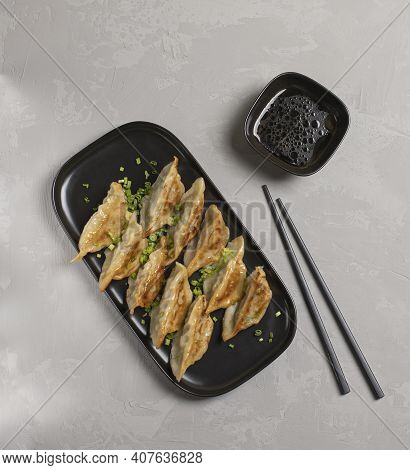 Fried Japanese Gyoza Dumplings On Black Plate With Chopsticks And Soy Sauce Top View. . High Quality