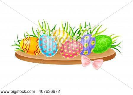 Painted Easter Eggs Or Paschal Eggs Rested On Wooden Board With Green Grass And Lily Of The Valley F