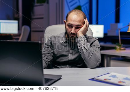 Tired Businessman Sit At The Computerin The Evening Works On Deadline. Workaholic Employee Falling A