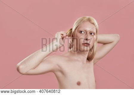 Young Caucasian Man Combing His Long Blond Hair While Standing On Pink Background And Looking To Sid