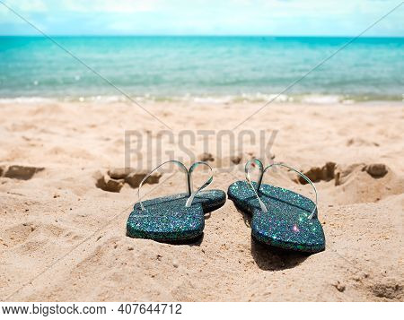 Blue Flipflop On Sand Beach At Coast With Blue Sea And Blue Sky Blured.accessories For Travel Summer