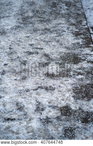 De-icing Chemicals On The Pavement. Pavement Is Sprinkled With Technical Salt Or Salt Mixtures Based
