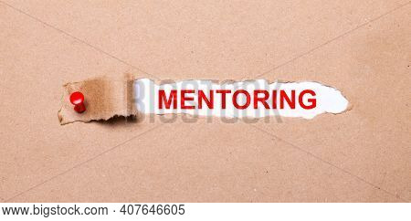 Beneath The Torn Strip Of Kraft Paper Attached With A Red Button Is A White Paper Labeled Mentoring