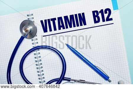 On A Light Blue Background, An Open Notebook With The Word Vitamin B12, A Blue Pen And A Stethoscope