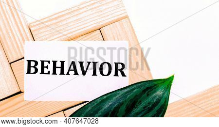 On A White Background Wooden Building Blocks, A White Card With The Text Behavior And A Green Leaf O
