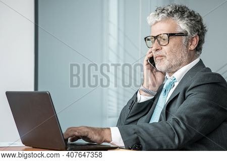 Serious Confident Businessman In Suit And Glasses Talking On Mobile Phone, Working At Computer In Of