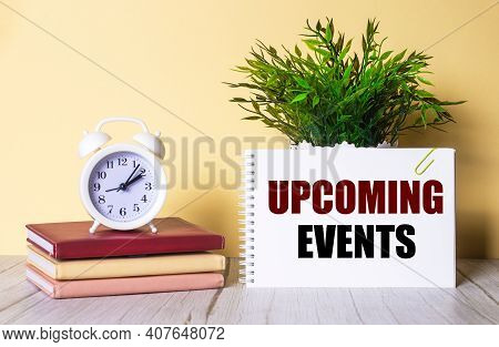 Upcoming Events Is Written In A Notebook Next To A Green Plant And A White Alarm Clock, Which Stands