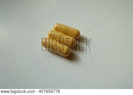 Three Orange Cellulose Capsules Of Multivitamins Dietary Supplement