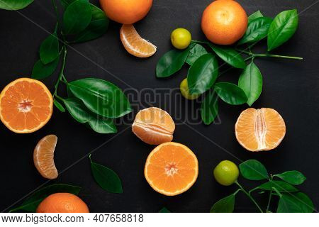 Tangerines Or Clementines With Leaves On A Black Background. Top View With Copy Space.