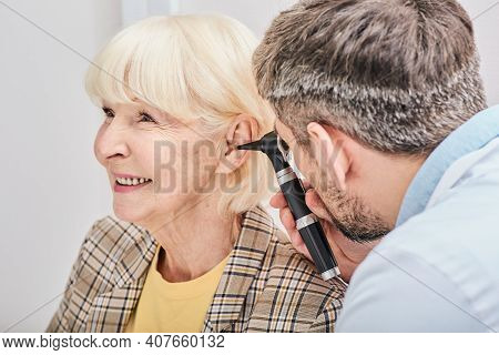 Elderly Woman During Ear Exam At A Hearing Clinic. Audiologist Examining Elderly Patient Ear Using O