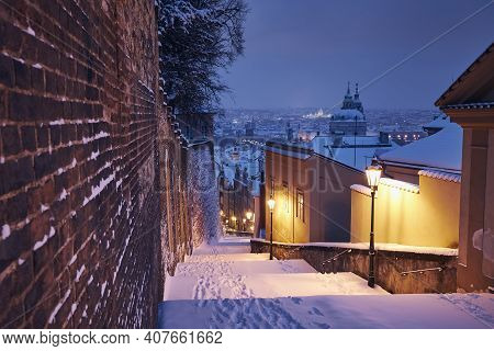 Cityscape Of Prague In Winter. Illuminated Historical Staircase Against Lesser Town And Old Town Ear