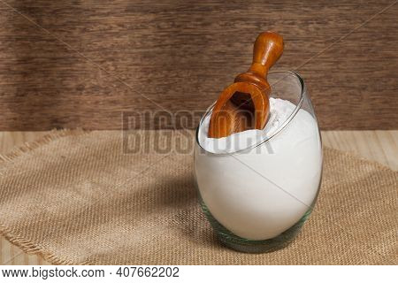 Baking Soda (sodium Bicarbonate) In A Glass Container; Photo On Wooden Background.