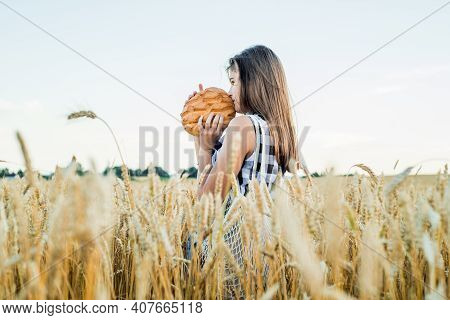 Field With Ears Of Corn, Harvest Of Bread.teenager Girl Holding Round Bread. Bread Selective Focus.