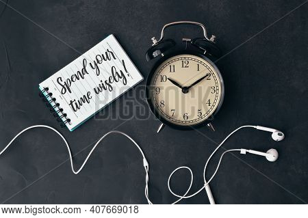 Top View Of Clock, Earphones And Notebook Written With Spend Your Time Wisely!