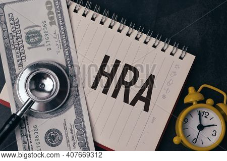 Top View Of Clock, Stethoscope, Money And Notebook Written With Hra Stands For Health Reimbursement