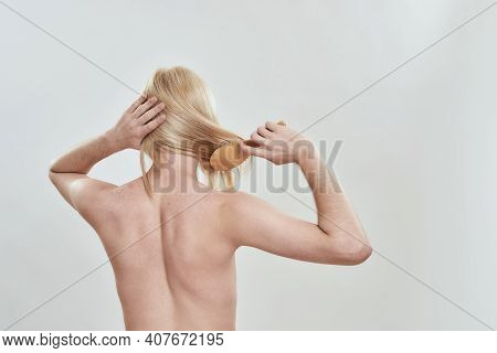 Rear View Of Young Shirtless Man Combing His Long Fair Hair Using Wooden Comb While Standing On Whit