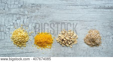 Oat Flakes, Corn Flakes, Millet Flakes And Oat Bran On On The Table.