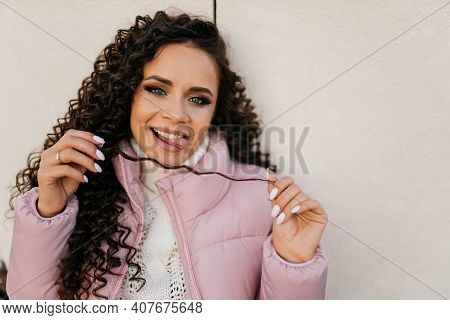 Close-up. A Girl With A Crafty Smile Playfully Holds Her Tongue Over Her Teeth And Straightens Her C