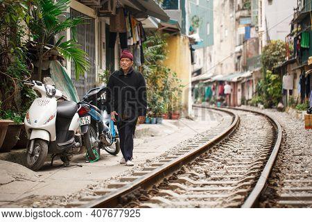 Hanoi, Vietnam, January 13, 2018: A Vietnamese Man Walks Along The Railroad Along The Houses In The