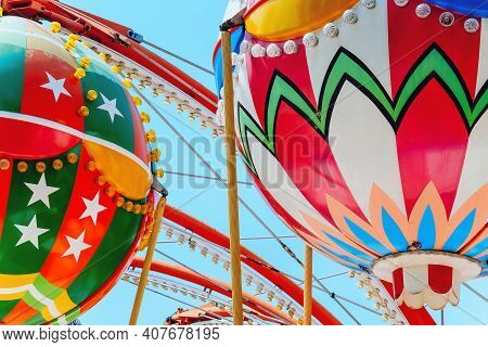 Close Up Image Of Ferris Wheel With Multi-coloured Cabins Against The Sky.