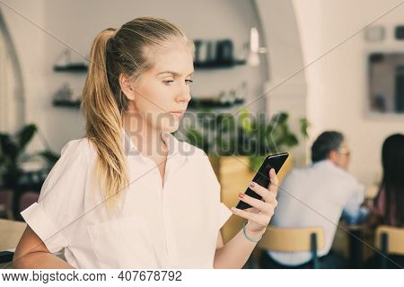 Serious Beautiful Young Woman Wearing White Shirt, Using Smartphone, Typing Message, Standing In Co-