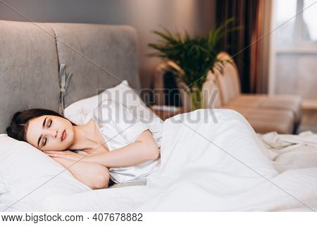 Young Girl Sleeping In Bed. Morning Or Evening In Bed With The Female Model. Brunette In Silk Pajama