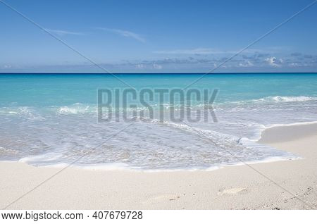 Panoramic View Of A Wild And Deserted Tropical Beach With The Transparent Caribbean Sea And The Blue