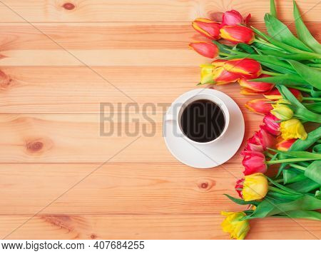 White Cup Of Coffee And Colorful Fresh Spring Tulips As Border On Wooden Table. Top View, Copy Space