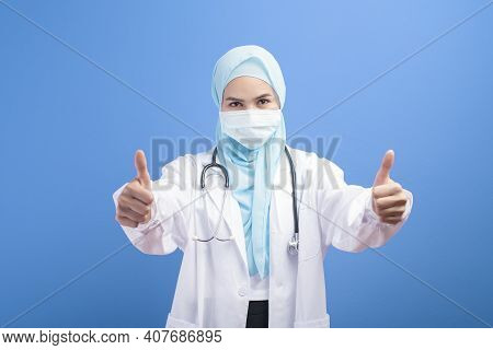 Female Muslim Doctor With Hijab Wearing A Surgical Mask Over Blue Background Studio.