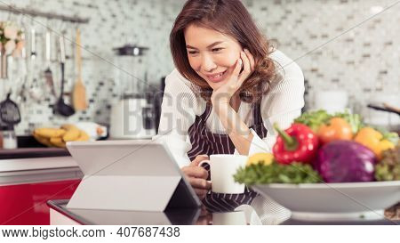 Asian Cute Middle-age Woman Holding Coffee Cup And Using Tablet Computer Connect To Internet In Kitc