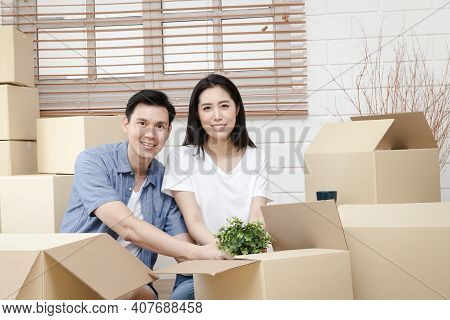Asian Couple Moving Into A New Home Help Unpack The Brown Paper Box To Decorate The House. Concept O