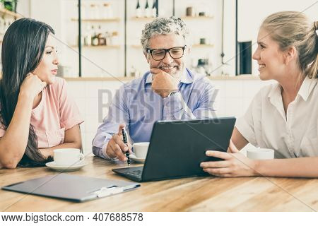 Happy Female Manager Presenting Project On Laptop To Young Woman And Mature Man, Discussing Content