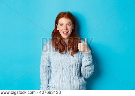 Impressed Redhead Girl Showing Thumb Up And Staring Amazed At Camera, Praising Good Work, Standing A