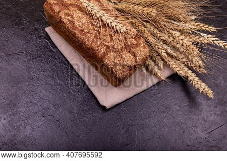 Rustic Sourdough Bread With Crispy Crust. Rye Bread On Dark Background. Loaf Of Whole Grain Bread An