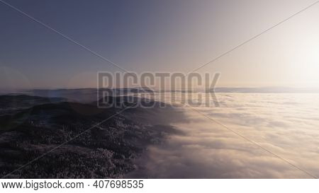 Fog And Clouds In A Valley At Sunset In A Wilderness Winter Wonderland.