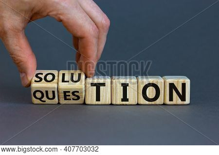 Question And Solution Symbol. Businessman Turns Wooden Cubes And Changes The Word 'question' To 'sol