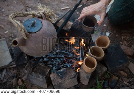 A Steaming Teapot And Tea Cups. Tea Preparation In A Clay Pot On A Fire. A Camping Trip, A Journey.