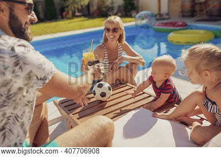 Beauitful Young Family Spending Hot Sunny Summer Day By The Swimming Pool, Parents Making A Toast An