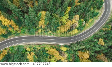 View Of A Winding Mountain Road In Autumn. Top View From Drone On Winding Road In Forest. Colorful L