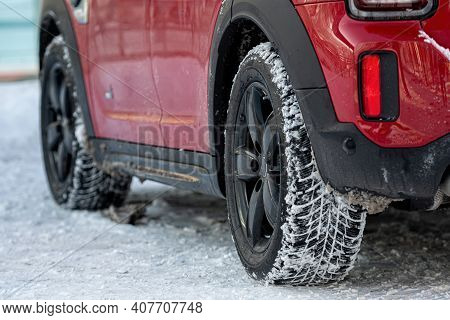 Close-up Rear View Of A Red Car On Parking,, Dirty Rear Wheel Tire On Snow