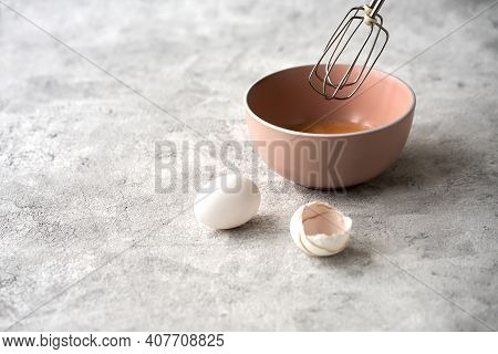 A Ceramic Bowl With Beaten Eggs And A Fragment Of A Whisk From The Mixer Above It. Next To The Bowl