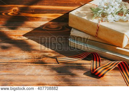 A St. George Ribbon And A Stack Of Old Books On A Wooden Background With A Sprig Of A Flowering Tree