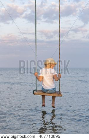 Boy Sitting On Rope Swing Over The Water. Swing On Beach. Vertical Frame