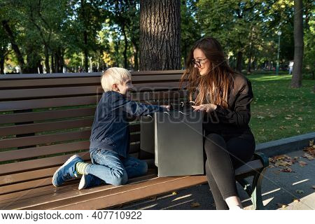 Child Boy And Nanny Are Sitting On Bench In Park And Considering Shopping Bags.