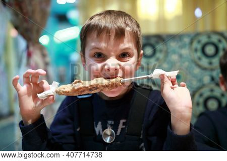 Boy Eating Kebab On Skewer